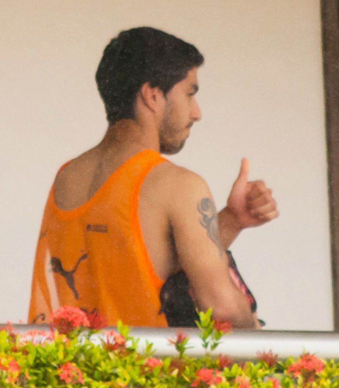 Uruguay's Luis Suarez gives a thumbs-up from a balcony of the team's hotel in Natal