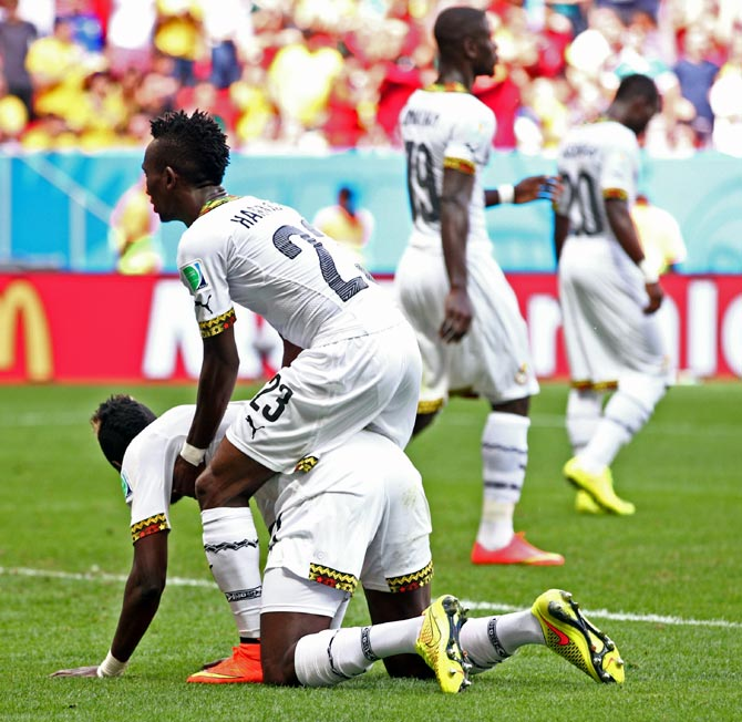 Harrison Afful consoles John Boye of Ghana after he scored an own goal