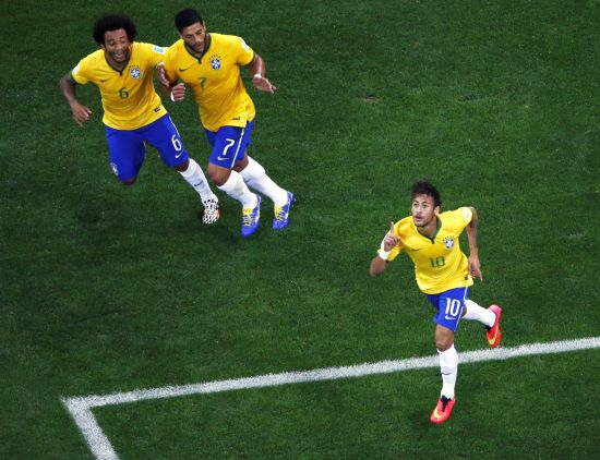 Brazil's Neymar, right, celebrates with teammates Marcelo, left, and Hulk after scoring