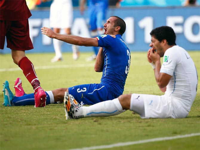 Uruguay's Luis Suarez (right) reacts after biting Italy's Giorgio Chiellini