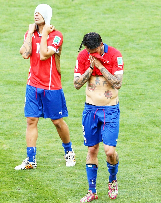 Jorge Valdivia and Mauricio Pinilla of Chile look dejected after being defeated by Brazil in the penatly shootout