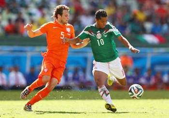 Giovani dos Santos of Mexico beats Daley Blind of the Netherlands to the ball, shoots and scores to put his team into the lead in the World Cup Brazil Round of 16 match.