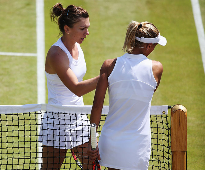 Simona Halep of Romania shakes hands with Lesia Tsurenko of Ukraine