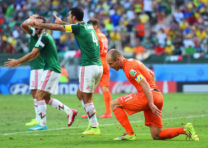 Arjen Robben of the Netherlands and Rafael Marquez of Mexico react the referee awarded the penalty to The Netherlands during their World Cup last 16 match on Sunday