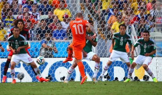 Wesley Sneijder of the Netherlands shoots and scores his team's first goal past Guillermo Ochoa of Mexico
