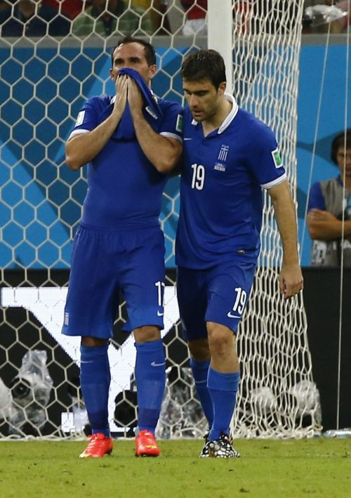 Greece's Theofanis Gekas, left, reacts after missing his penalty kick as team mate Sokratis Papastathopoulos consoles him