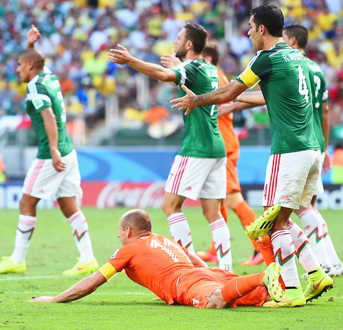 Rafael Marquez of Mexico reacts after a challenge on Arjen Robben of the   Netherlands resulting in a yellow card for Marquez and a penalty kick for the Netherlands