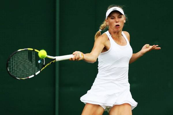 Caroline Wozniacki of Denmark plays a forehand during her first round match against Shahar Peer of Israel