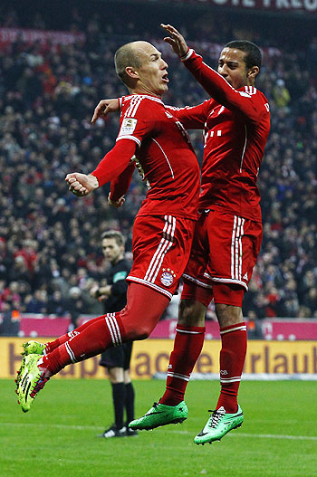 Bayern Munich's Arjen Robben (L) and Thiago jump in the air while celebrating a goal during their German Bundesliga match against Schalke 04 in Munich on Saturday