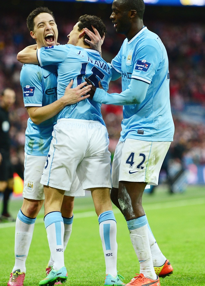 Samir Nasri, left, Yaya Toure, right, celebrate with goalscorer Jesus Navas of Manchester City.