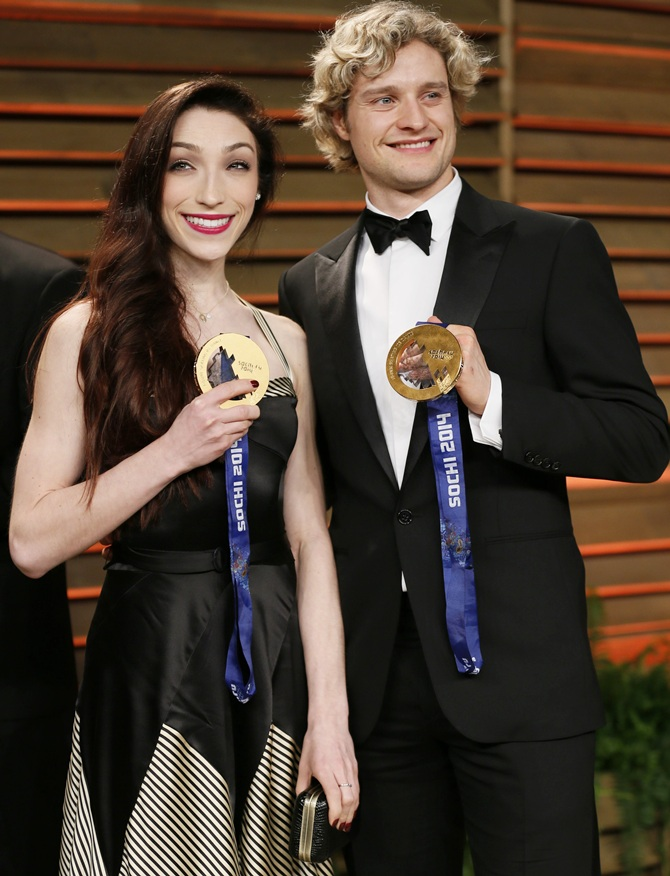 Ice dancers Meryl Davis and Charlie White, right, hold up their gold medals.