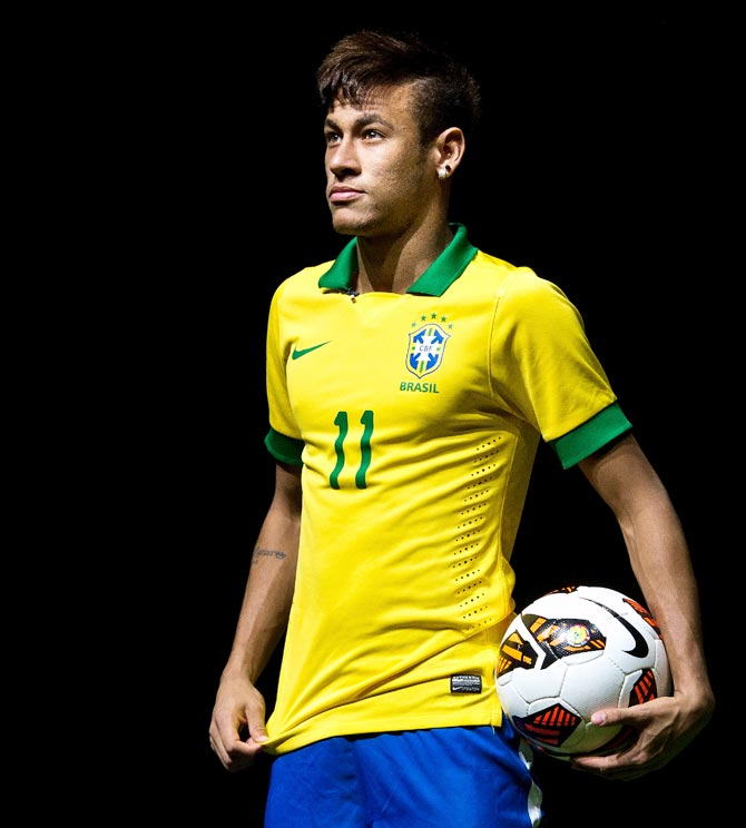 Neymar poses with Brazil's new jersey for the 2014 FIFA World Cup.