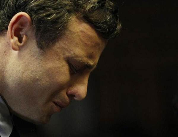 Olympic and Paralympic running star Oscar Pistorius reacts ahead of court proceedings at the Pretoria Magistrates court, August 19, 2013