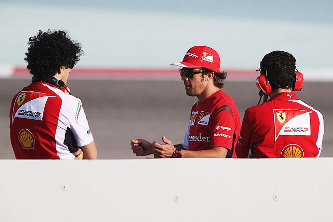 Fernando Alonso (centre) of Spain and Ferrari