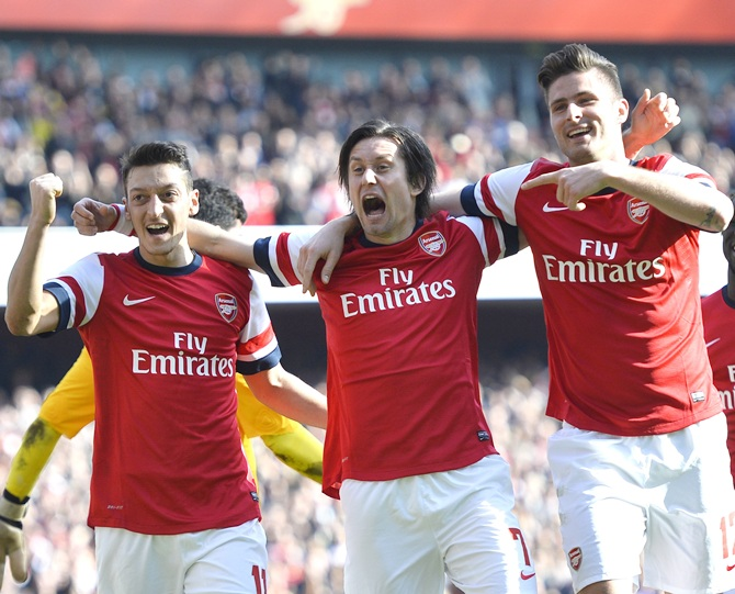 From left, Arsenal's Mesut Ozil, Tomas Rosicky and Olivier Giroud celebrate.