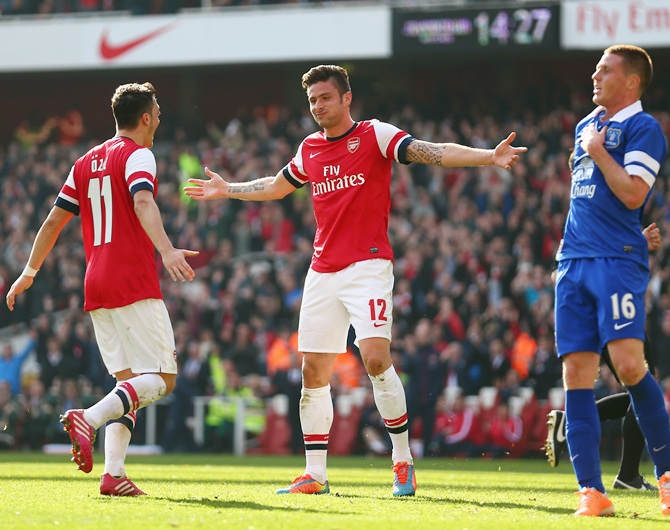 Olivier Giroud of Arsenal celebrates with teammate Mesut Oezil after scoring his team's fourth goal.
