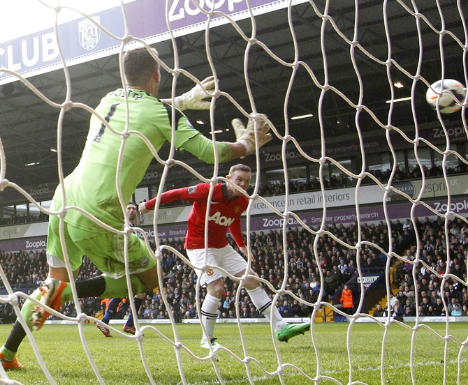Manchester United's Wayne Rooney,right, scores a goal during their English Premier League match against West Bromwich Albion.