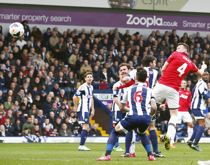 Manchester United's Phil Jones,right, scores a goal against West Bromwich Albion.