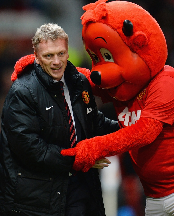Manchester United Manager David Moyes is greeted by mascot Fred the Red.