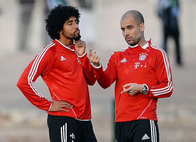 Head coach Josep Guardiola speaks to Dante during a Bayern Munich training session