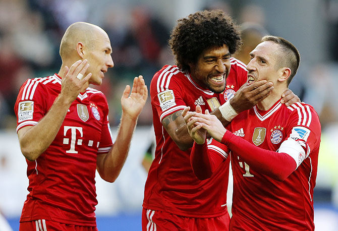 Bayern's Franck Ribery of France (right) celebrates with teammates Arjen Robben (left) and Dante after scoring against Wolfsburg during their German Bundesliga match in Wolfsburg, on Saturday