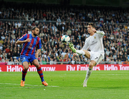 Cristiano Ronaldo (R) of Real Madrid CF controls the ball beside Loukas Vyntra of Levante UD during the La Liga match on Sunday