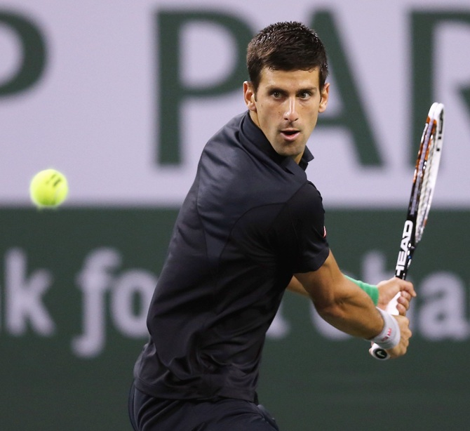 Novak Djokovic of Serbia returns a backhand to Victor Hanescu of Romania during the BNP Paribas Open