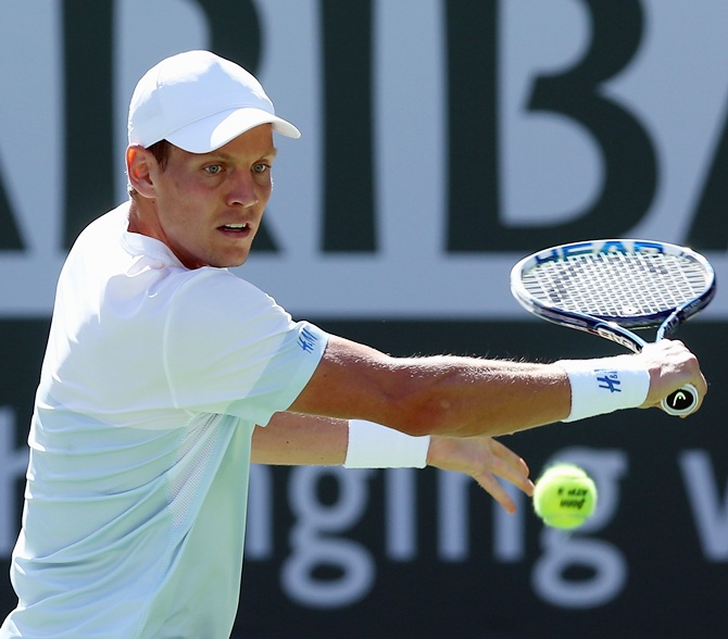 Tomas Berdych of the Czech Republic returns a backhand to Roberto Bautista Agut of Spain