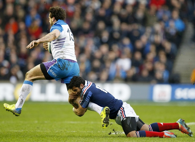 Alex Dunbar is tackled by France's Maxime Mermoz