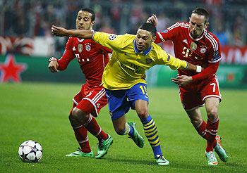 Bayern Munich's Thiago Alcantara and Franck Ribery (right) tackle Arsenal's Alex Oxlade-Chamberlain during their Champions League round of 16 second leg match in Munich, on Tuesday