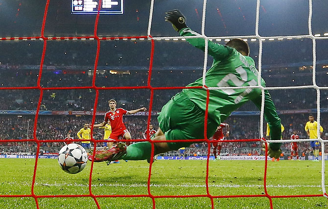 Arsenal's Lukasz Fabianski saves a penalty shot by Bayern Munich's Thomas Mueller (left) on Tuesday