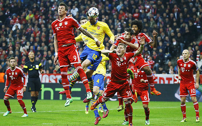 Bayern Munich's Mario Mandzukic (2nd from left ) is beaten by Arsenal's Olivier Giroud (12) in an aerial challenge