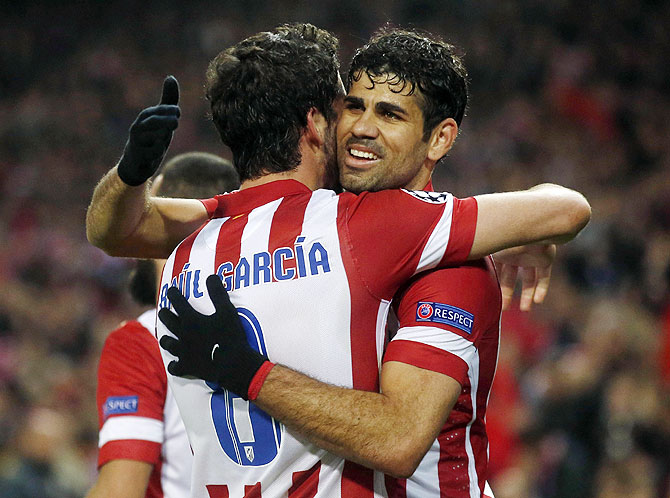 Atletico Madrid's Raul Garcia and teammate Diego Costa (right) celebrate after beating AC Milan in their Champions League last 16 second leg match at Vicente Calderon stadium in Madrid on Tuesday