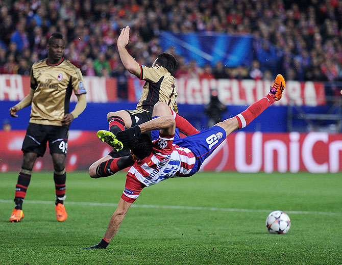 Diego Costa (right) of Atletico Madrid clashes with Adil Rami of AC Milan during their match on Tuesday