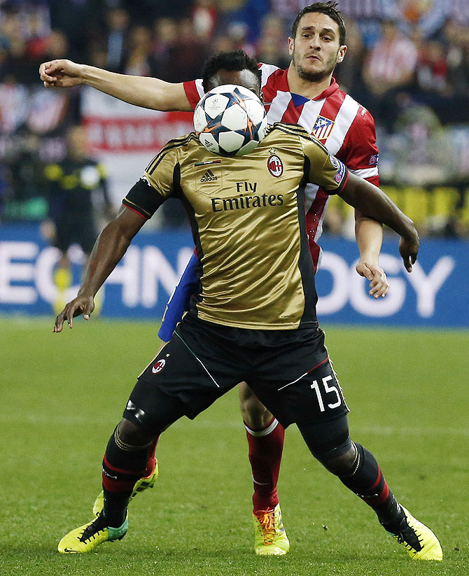 Atletico Madrid's Koke (back) and AC Milan's Michael Essien vie for possession on Tuesday
