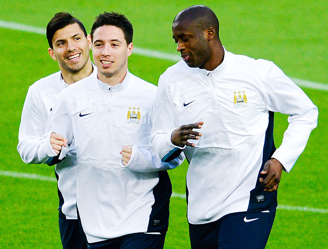 Manchester City FC players Sergio Aguero (left), Samir Nasri (centre) and Yaya Toure warm up during a training session on Tuesday