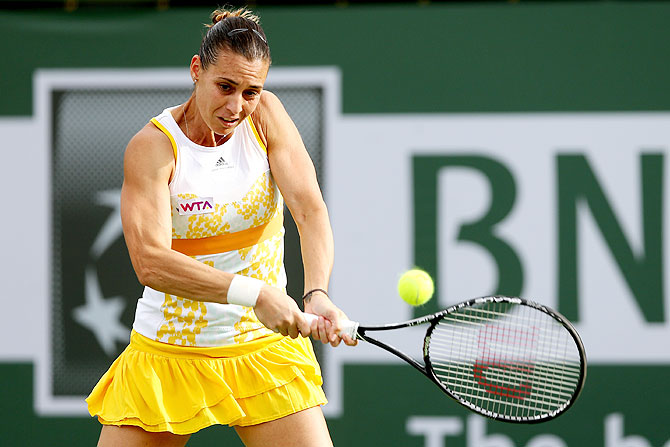Flavia Pennetta of Italy returns a shot to Camila Giorgi of Italy