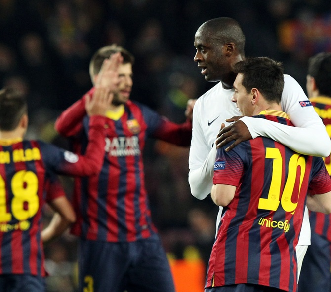 Barcelona's Lionel Messi, right, is embraced by Manchester City's Yaya Toure after their Champions League last 16 second leg match