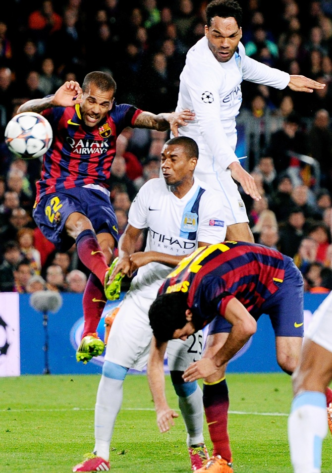Joleon Lescott of Manchester City rises above Daniel Alves of Barcelona to head the ball