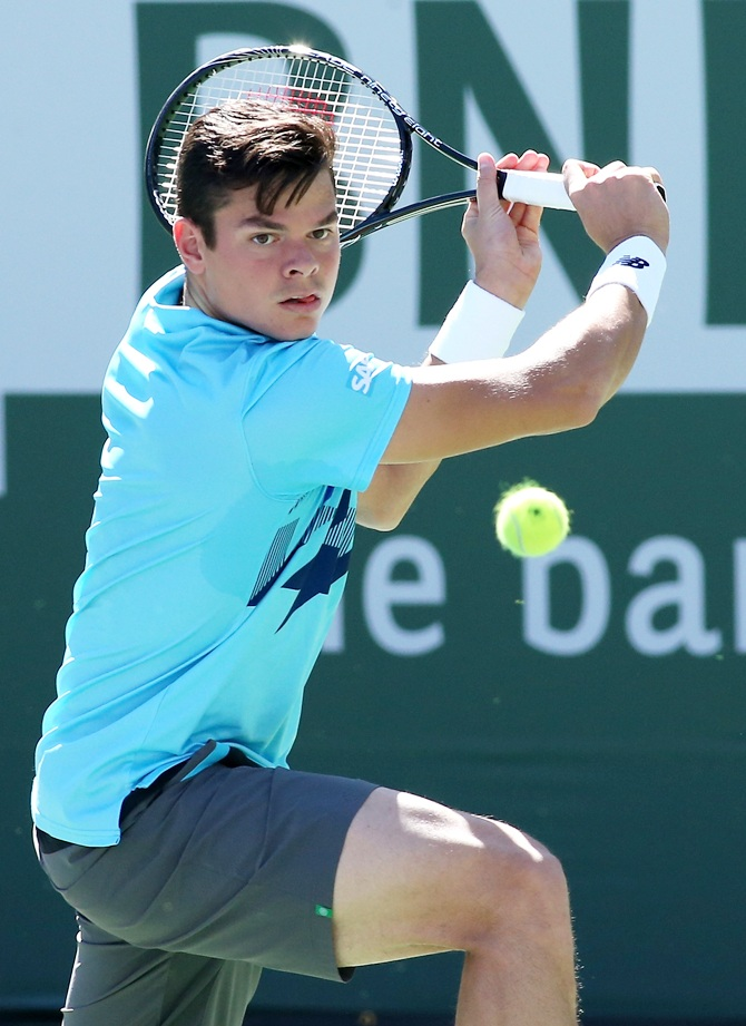 Milos Raonic of Canada hits a return to Andy Murray of Great Britain
