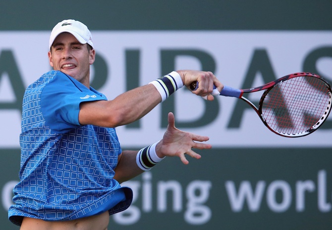 John Isner follows through on a forehand to Fernando Verdasco of Spain