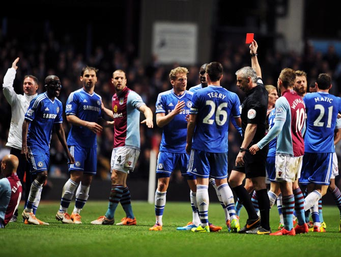 Referee Chris Foy shows Chelsea's Ramires the red card after a challenge on Karim El Ahmadi of Aston Villa