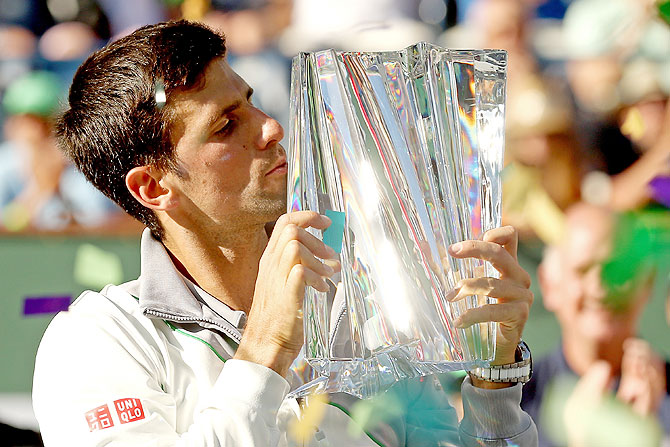Novak Djokovic of Serbia kisses the trophy after defeating Roger Federer of Switzerland to win the Indian Wells final on Sunday
