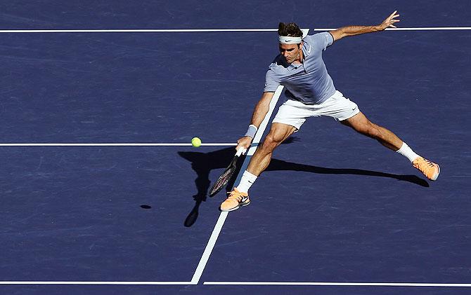 Roger Federer of Switzerland returns a backhand volley to Novac Djokovic of Serbia on Sunday