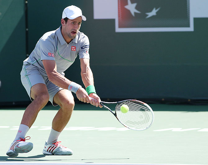 Novak Djokovic of Serbia hits a return to Roger Federer of Switzerland on Sunday