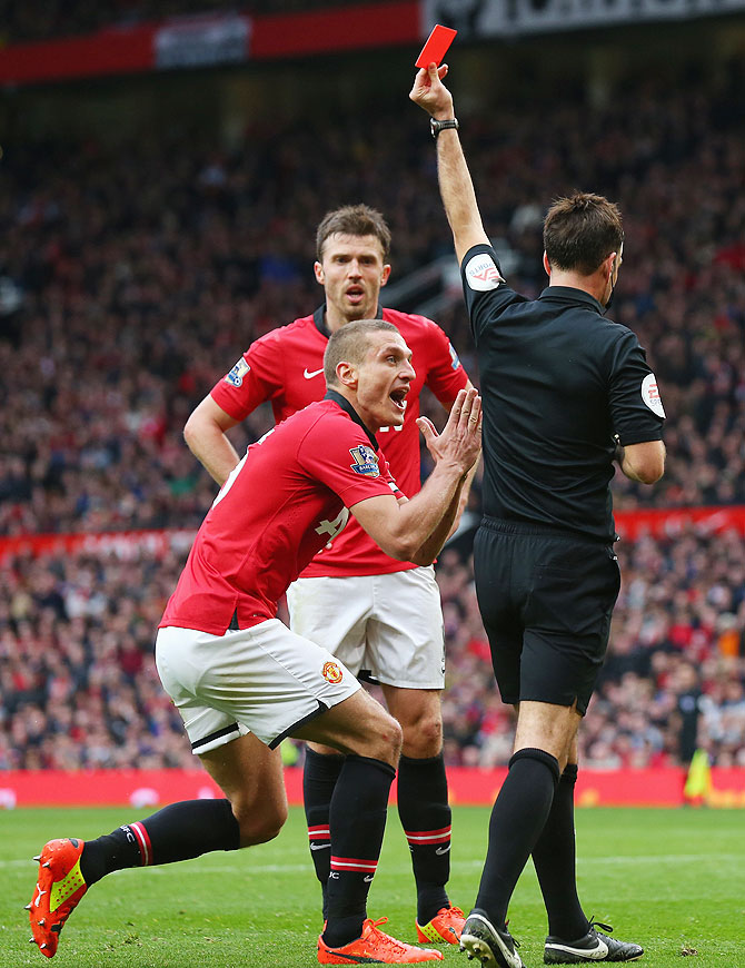 Nemanja Vidic of Manchester United is shown a red card by referee Mark Clattenburg for fouling Liverpool's Daniel Sturridge on Sunday