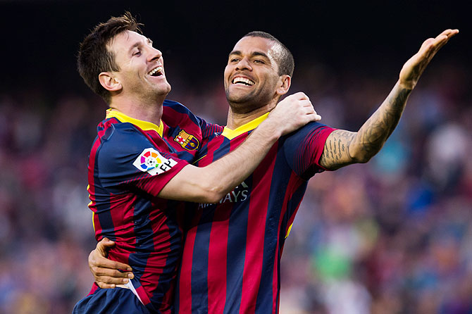 FC Barcelona's Lionel Messi celebrates with teammate Daniel Alves after scoring against Osasuna during their La Liga match on Sunday
