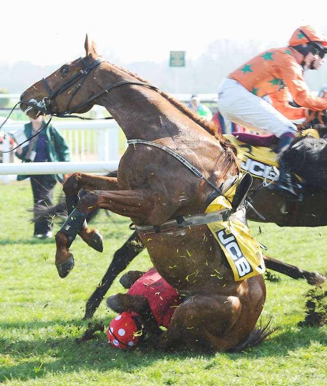 Ruby Walsh and Abbyssial fall in the JCB Triumph Hurdle during the Cheltenham Festival at Cheltenham Racecourse