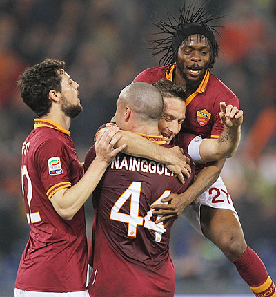Francesco Totti (centre) of AS Roma celebrates with his teammates after scoring on Monday