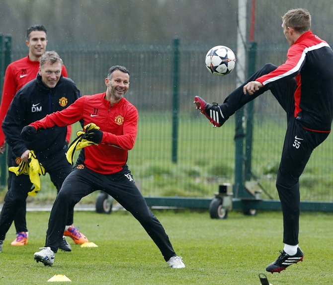 From left, Manchester United's Robin Van Persie, manager David Moyes and Ryan Giggs laugh as Darren Fletcher jumps for the ball during a training session